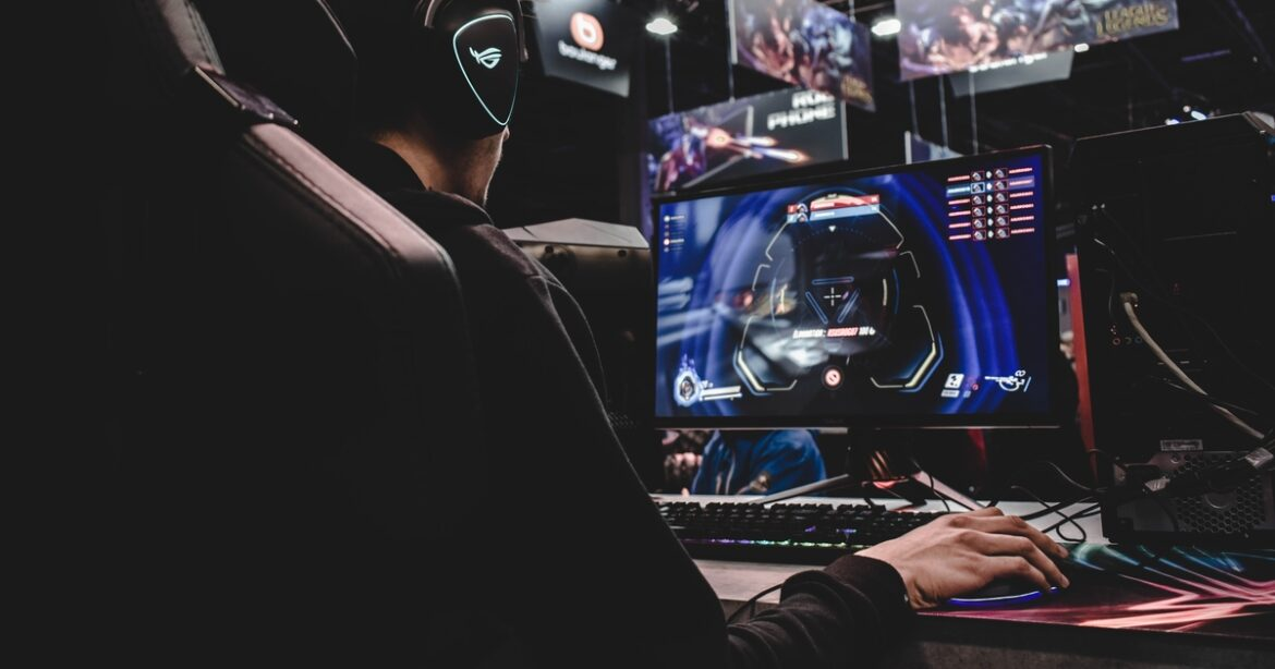 Esports player in front of computer, hand on joystick